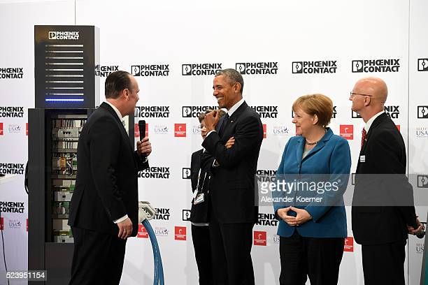 S President Barack Obama and German Chancellor Angela Merkel get a presentation at the Phoenix Contact stand by CEO of Phoenix Contact Frank...