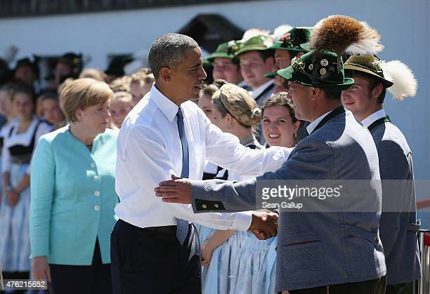 S President Barack Obama and German Chancellor Angela Merkel greet locals dressed in traditional Bavarian folk dress before the two leaders were...