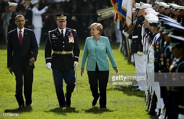 US President Barack Obama and German Chancellor Angela Merkel inspect the troops as they participate in an arrival ceremony on the South Lawn of the...