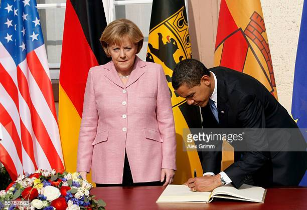 President Barack Obama and German Chancellor Angela Merkel smile as they sign the Golden Book of the city of Baden Baden in the City Hall upon...