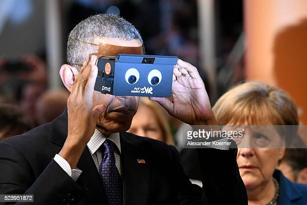 S President Barack Obama and German Chancellor Angela Merkel test virtual reality glasses at the ifm electronics stand at the Hannover Messe...