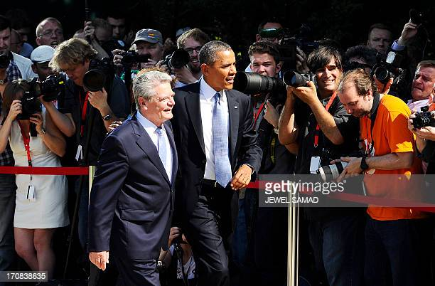 US President Barack Obama and German President Joachim Gauck walk past photojournalists after reviewing a guard of honor at the Schloss Bellevue in...