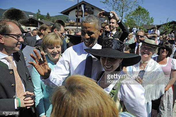 President Barack Obama and Germany's Chancellor Angela Merkel wave to guests after a breakfast meeting with local citizens dressed in Bavarian...