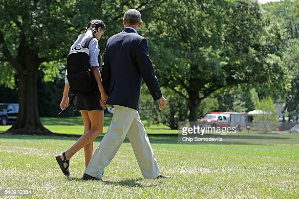 S President Barack Obama and his daughter Malia Obama walk out of the White House handinhand before boarding Marine One on the South Lawn June 17...