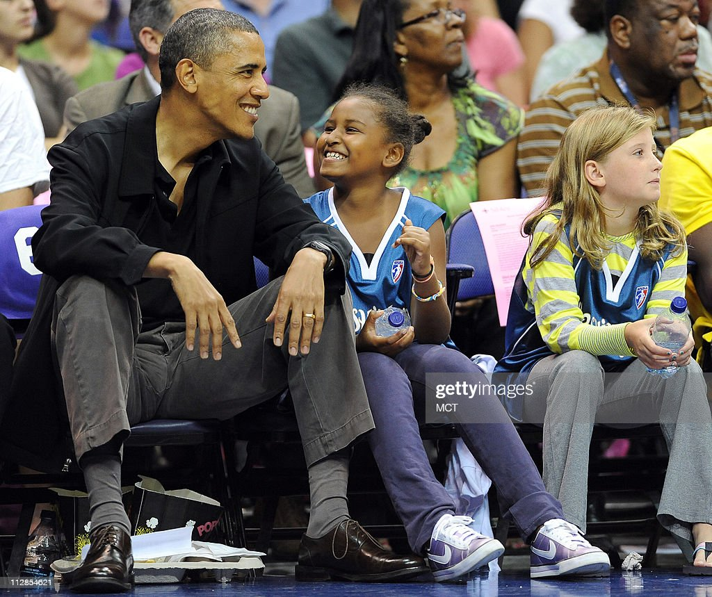President Barack Obama and his daughter, Sasha, enjoy a chuckle while watching the time-out entertainment on the floor during the game between the Washington Mystics and Tulsa Shock. The Mystics defeated the Shock, 87-62, at the Verizon Center in Washington, D.C., Sunday, August 1, 2010.