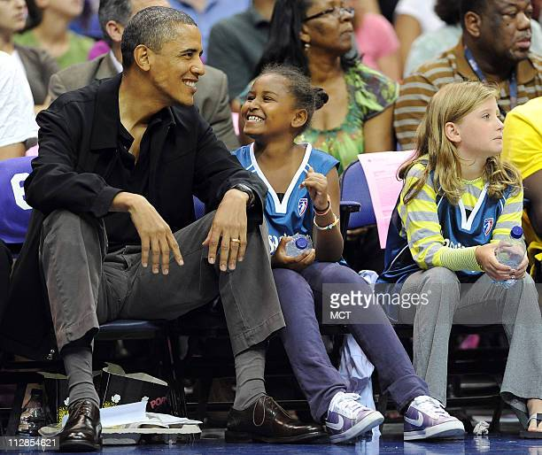 President Barack Obama and his daughter Sasha enjoy a chuckle while watching the timeout entertainment on the floor during the game between the...