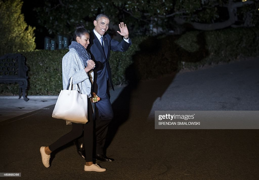 US President Barack Obama and his daughter Sasha walk to Marine One helicopter on the South Lawn of the White House December 19, 2014 in Washington, DC. Obama and the first family travel to Hawaii for a holiday vacation.