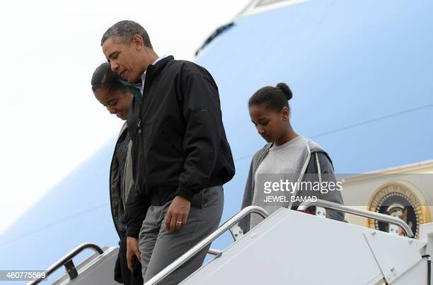 US President Barack Obama and his daughters Maila and Sasha disembark from Air Force One at Andrews Air Force Base in Maryland on January 5 2014...