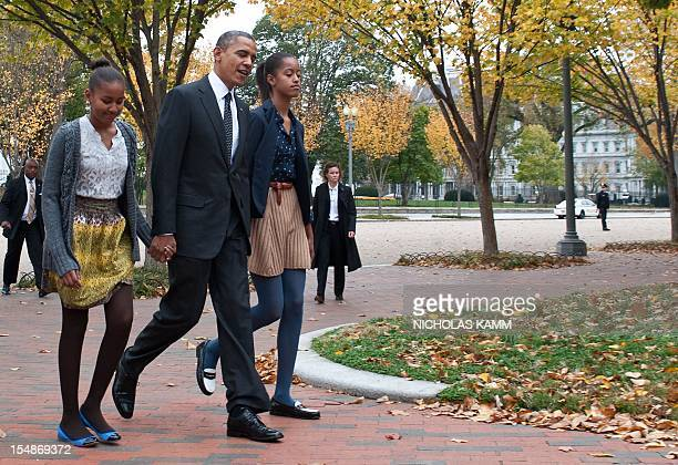 President Barack Obama and his daughters Malia and Sasha walk across Lafayette Park outside the White House in Washington on October 28, 2012 on...