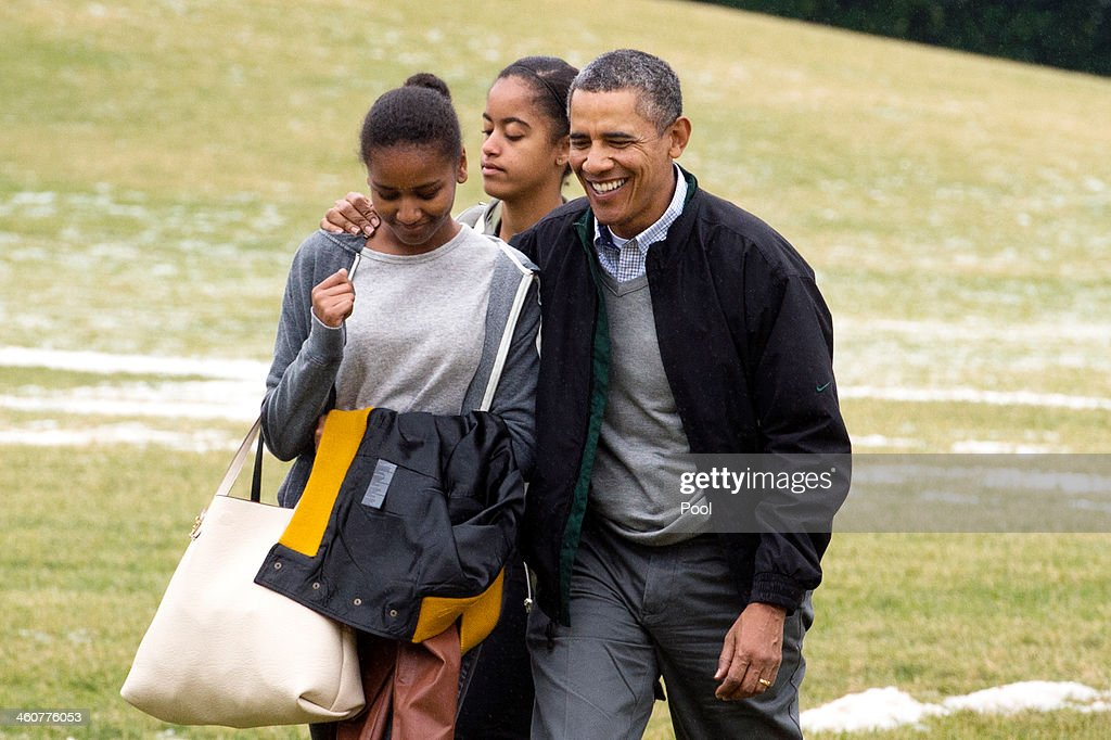 U.S. President Barack Obama (R) and his daughters Malia (C) and Sasha (L) walk across the South Lawn of the White House after arriving by Marine One January 5, 2014 in Washington, DC. Obama returns from a two-week holiday in Hawaii.