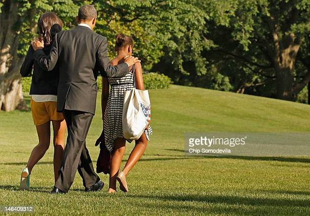 S President Barack Obama and his daughters Malia Obama and Sasha Obama walk across the South Lawn before boarding Marine One and departing the White...