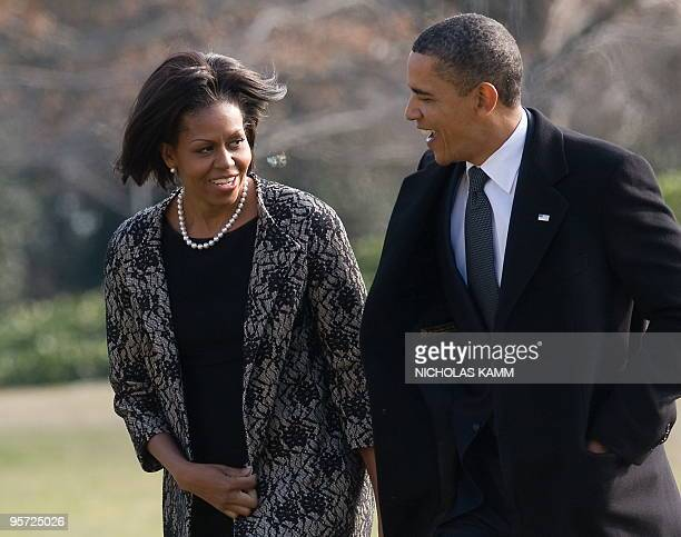 US President Barack Obama and his wife Michelle walk after disembarking from Marine One upon returning to the White House in WashingtonDC on January...