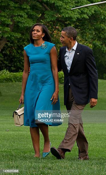 President Barack Obama and his wife Michelle walk from Marine One to the White House in Washington on May 5, 2012 after returning from campaign stops...