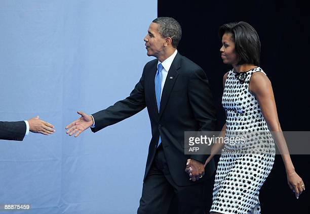 US President Barack Obama and his wife Michelle walk to the podium at the graduation ceremony of the New Economic School in Moscow on July 7 2009 The...