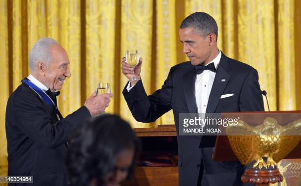 President Barack Obama and Israeli President Shimon Peres toast prior to Peres receiving the Presidential Medal of Freedom June 13, 2012 during a...