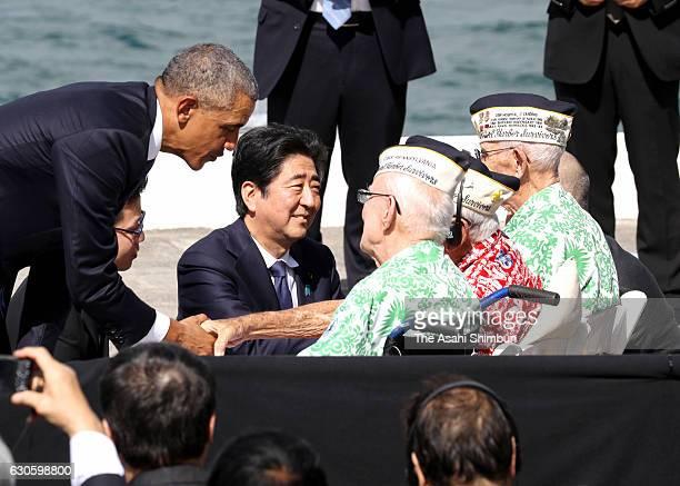 US President Barack Obama and Japanese Prime Minister Shinzo Abe greet Pearl Harbor survivors at Joint Base Pearl Harbor Hickam's Kilo Pier on...