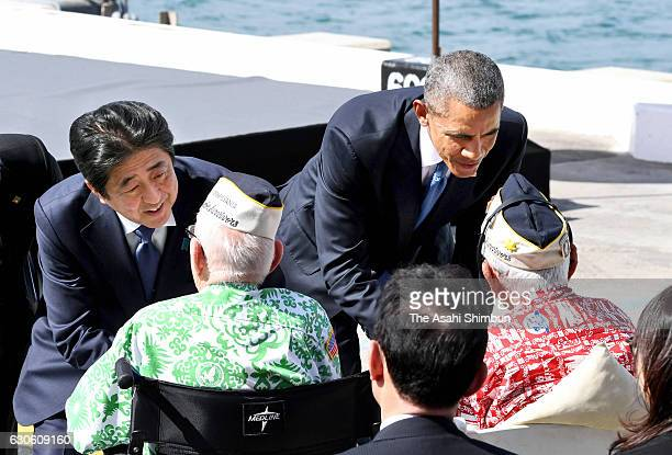 US President Barack Obama and Japanese Prime Minister Shinzo Abe greet Pearl Harbor survivors at Joint Base Pearl Harbor Hickam's Kilo Pier on...