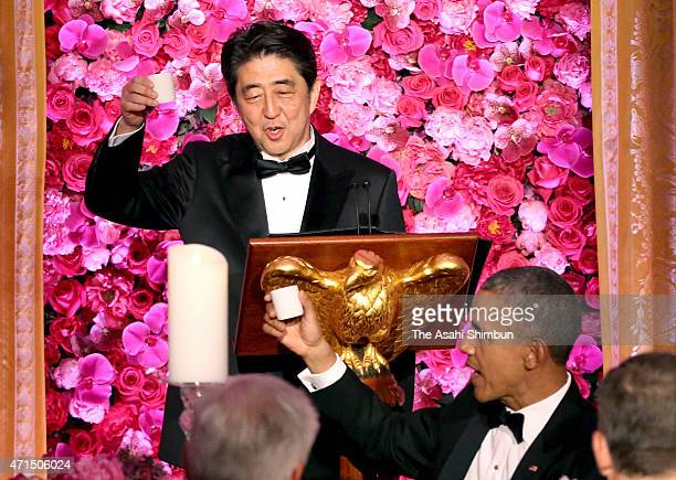 President Barack Obama and Japanese Prime Minister Shinzo Abe participate in a toast with sake during a state dinner at the East Room of the White...