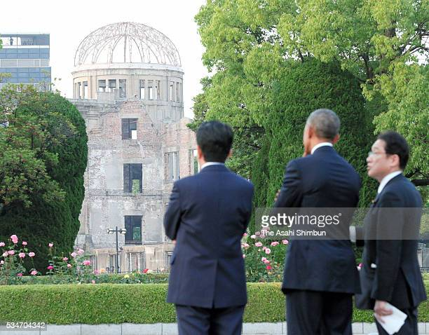 US President Barack Obama and Japanese Prime Minister Shinzo Abe listen to the explanation about the ABomb from Foreign Minister Fumio Kishida at the...