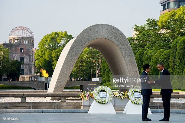 US President Barack Obama and Japanese Prime Minister Shinzo Abe shake hands after laying wreaths at the Hiroshima Peace Memorial Park in Hiroshima...