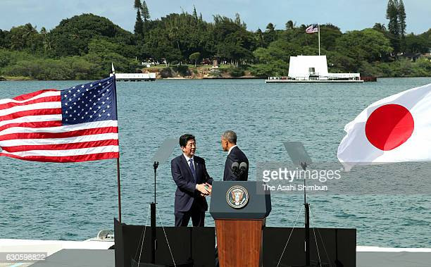 US President Barack Obama and Japanese Prime Minister Shinzo Abe shake hands after their remarks at Joint Base Pearl Harbor Hickam's Kilo Pier on...