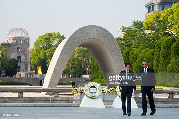 US President Barack Obama and Japanese Prime Minister Shinzo Abe turn around after laying wreaths during a visit to the Hiroshima Peace Memorial Park...