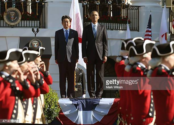US President Barack Obama and Japanese Prime Minister Shinzo Abe watch as a The Old Guard fife and drum corps passes by during an official arrival...