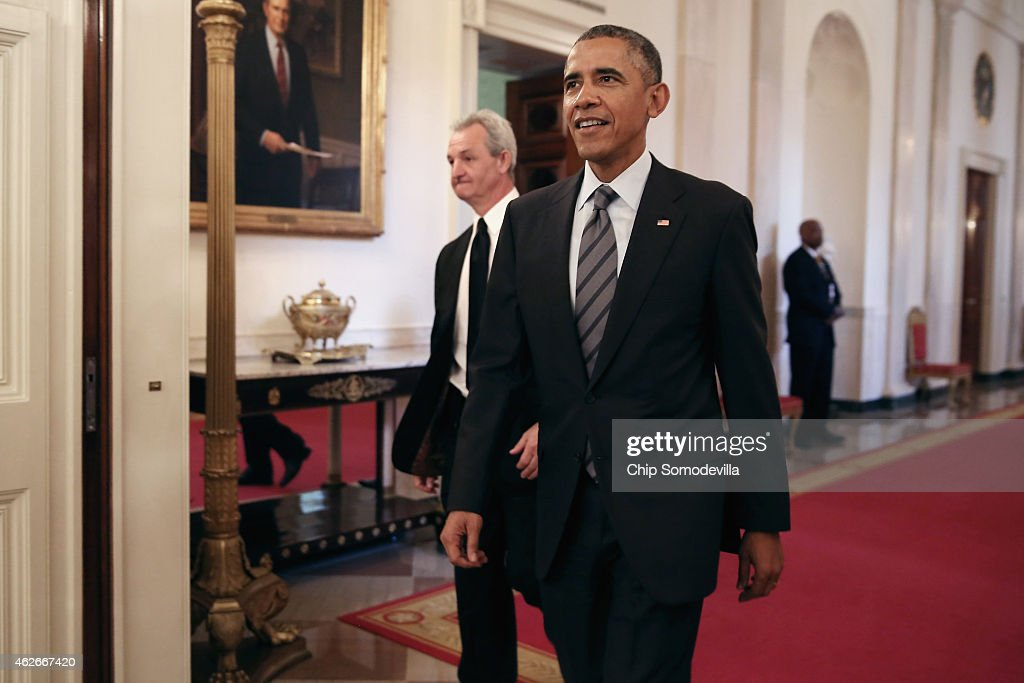 U.S. President Barack Obama (R) and National Hockey League champions Los Angeles Kings Head Coach Darryl Sutter walk into the East Room of the White House February 2, 2015 in Washington, DC. Obama simultaneously hosted the Kings and the Major League Soccer champions Los Angeles Galaxy. Both teams are owned in part by billionaire and The Weekly Standard publisher Philip Anschutz.
