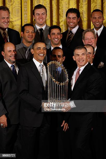 President Barack Obama and New York Yankees Manager Joe Girardi hold the Major League Baseball Commissioner's Trophy while posing for photographs...