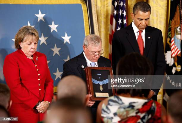 S President Barack Obama and Paul and Janet Monti bow their heads in prayer after the Medal of Honor was awarded to their son US Army Sergeant First...