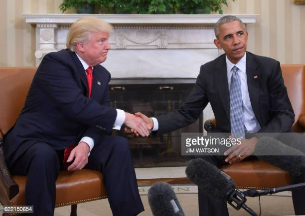 President Barack Obama and Presidentelect Donald Trump shake hands during a transition planning meeting in the Oval Office at the White House on...