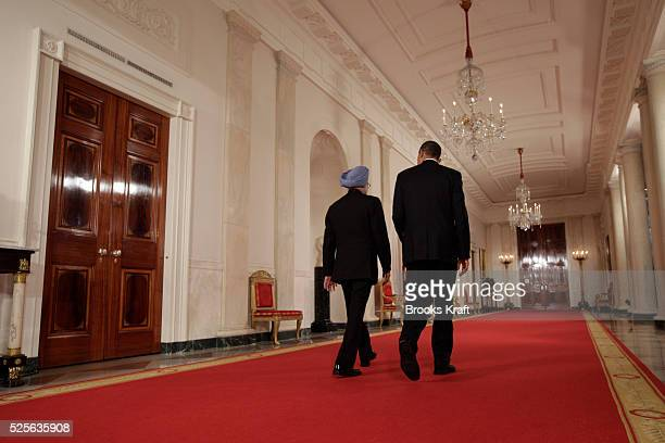 US President Barack Obama and Prime Minister Manmohan Singh walk down the Cross Hall on the way to a news conference in the East Room at the White...