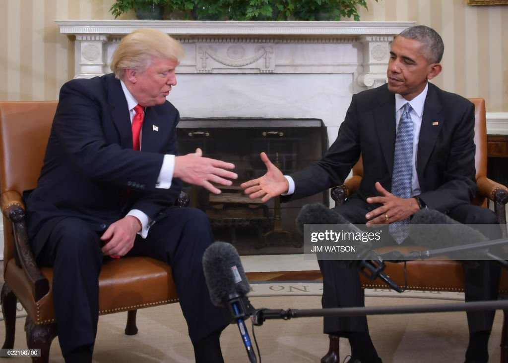 President Barack Obama and Republican President-elect Donald Trump shake hands during a transition planning meeting in the Oval Office at the White House on November 10, 2016 in Washington,DC. /