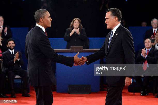 S President Barack Obama and Republican presidential candidate Mitt Romney shake hands prior to the start of a town hall style debate at Hofstra...