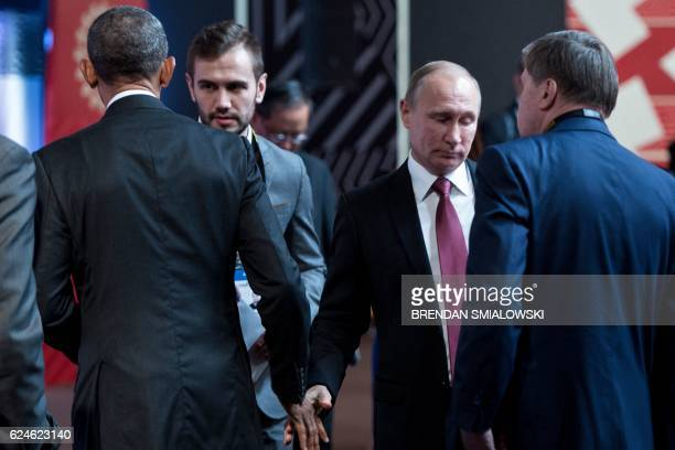 US President Barack Obama and Russia's President Vladimir Putin walk from each other after speaking and shaking hands before an economic leaders...