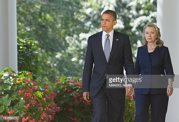 US President Barack Obama and Secretary of State Hillary Clinton make their way through the Colonnade to deliver a statement in the Rose Garden of...