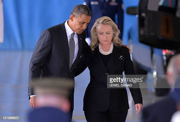 President Barack Obama and State Secretary Hillary Clinton return to thei seats after speaking during the transfer of remains ceremony marking the...
