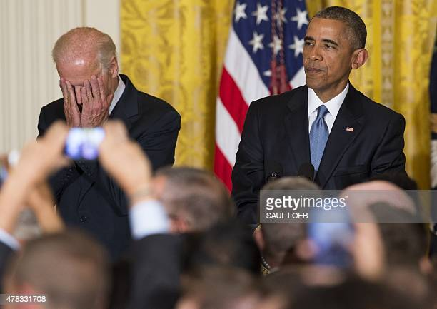 US President Barack Obama and US Vice President Joe Biden react to a heckler who interrupted the president's speech during a reception in honor of...