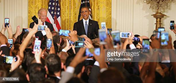 S President Barack Obama and Vice President Joe Biden attend a reception for LGBT Pride Month in the East Room of the White House June 24 2015 in...