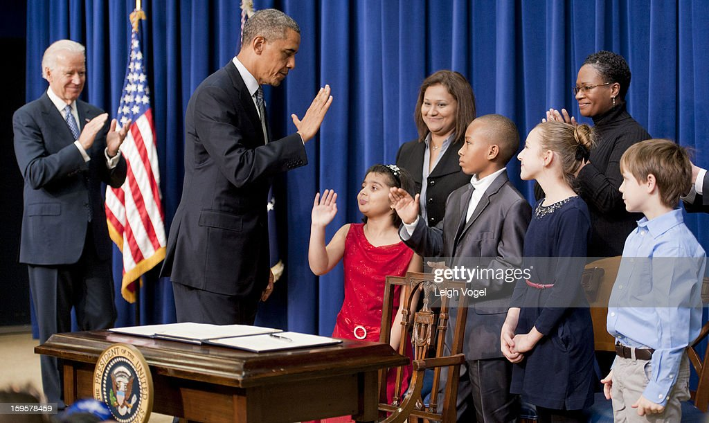 President Barack Obama and Vice President Joe Biden greet children who wrote letters to the White House expressing concern about gun violence before President Obama signs executive orders designed to reduce gun violence in the United States in the Eisenhower Executive Building on January 16, 2013 in Washington, DC.