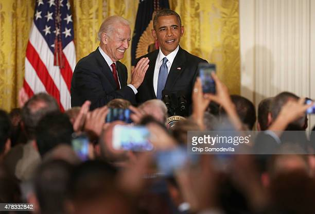 S President Barack Obama and Vice President Joe Biden react after a heckler is removed from a reception for LGBT Pride Month in the East Room of the...