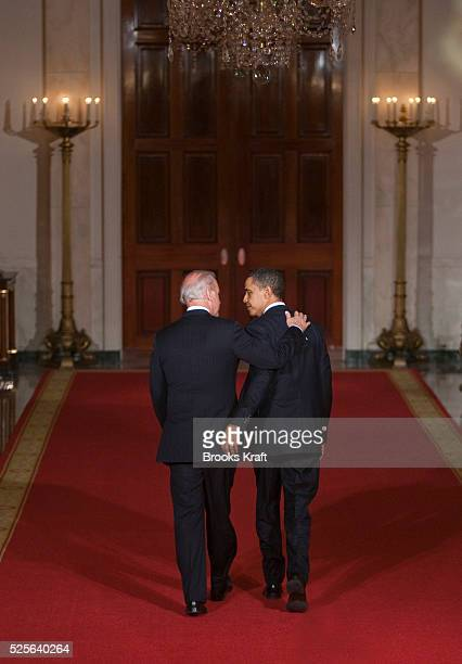 US President Barack Obama and Vice President Joe Biden walk arminarm in the Cross Hall of the White House in Washington following Obama's remarks in...