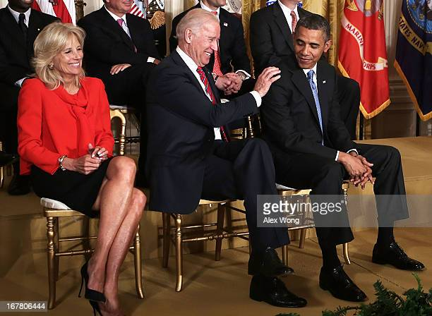 S President Barack Obama and Vice President Joseph Biden share a moment as Biden's wife Jill Biden looks on during a veterans employment event in the...
