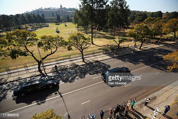 President Barack Obama and wife Michelle Obama are driven past the Union Buildings in the presidential motorcade to board Marine One on June 29 2013...