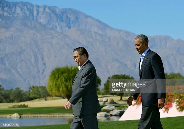 US President Barack Obama arrives alongside Laos' President Choummaly Sayasone for a group family photo during a meeting of the Association of...