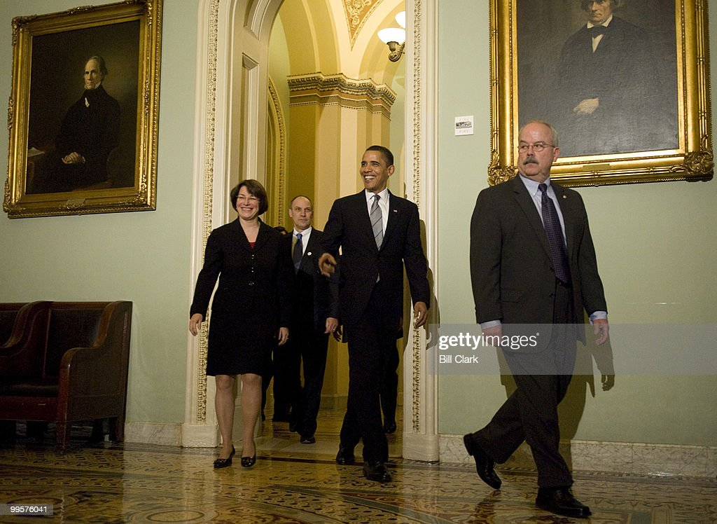 President Barack Obama arrives with Sen. Amy Klobuchar, D-Minn., left, and Senate Sergeant at Arms Terrance Gainer, right, for a lunch meeting to dicuss the budget with Senate Democrats in the U.S. Capitol on Wednesday, March 25, 2009.