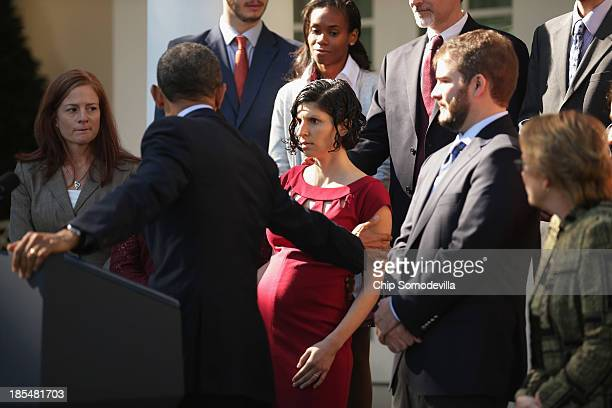 S President Barack Obama assists a woman who became dizzy during his remarks about the errorplagued launch of the Affordable Care Act's online...