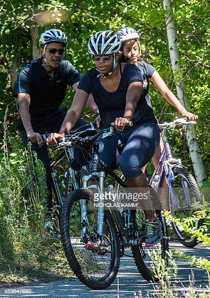 US President Barack Obama bikes with First Lady Michelle Obama and daughter Malia at Martha's Vineyard Massachusetts on August 15 2014 during their...