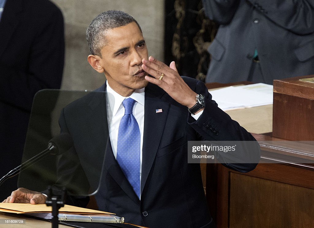 U.S. President Barack Obama blows a kiss to First Lady Michelle Obama, unseen, before delivering the State of the Union address to a joint session of Congress at the Capitol in Washington, D.C., U.S., on Tuesday, Feb. 12, 2013. Obama called for raising the federal minimum wage to $9 an hour and warned he'll use executive powers to get his way on issues from climate change to manufacturing if Congress doesn't act, laying out an assertive second-term agenda sure to provoke Republicans. Photographer: Joshua Roberts/Bloomberg via Getty Images