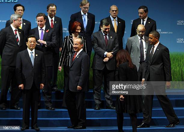 US president Barack Obama bottom right arrives while Hu Jintao China's president bottom left stands during a photo session at the G20 Seoul Summit...